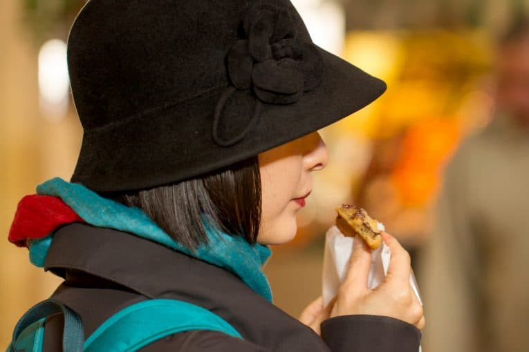 Mujer con sombrero comiendo