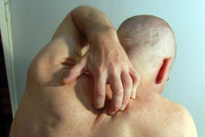 Un hombre intentando rascarse la espalda